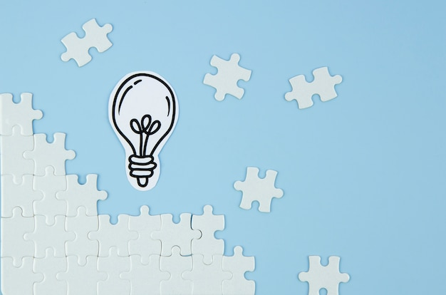 Pieces of puzzle with light bulb on blue background Premium Photo