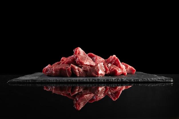 Pezzi di carne fresca cruda isolato sul nero sul bordo di pietra vista laterale con mirroring Foto Gratuite