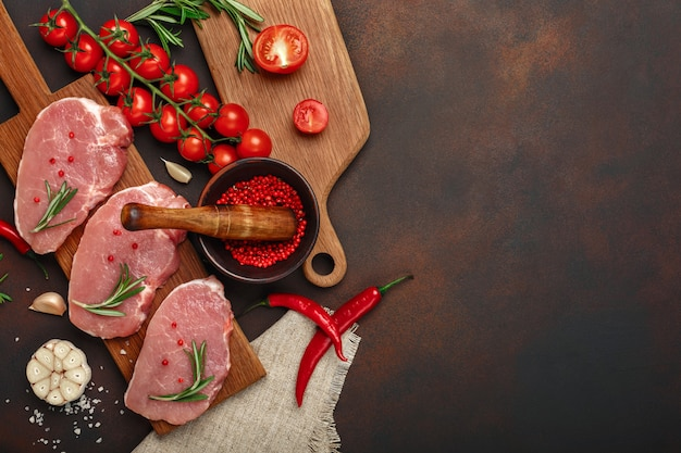 Pieces of raw pork steak on cutting board with cherry tomatoes, rosemary, garlic, pepper, salt and spice mortar Premium Photo