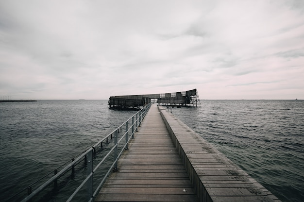 Pier leading to the ocean under the gloomy sky Free Photo