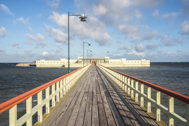 Pier surrounded by the sea and buildings under a cloudy sky and sunlight Free Photo