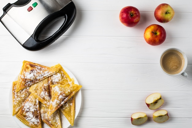 Pies lie on the table next to apples, a toaster and a cup of coffee Premium Photo