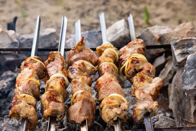 串に玉ねぎを添えた豚のシャシリク。ピクニック。火で揚げた肉。背景画像、コピースペース。 Premium写真