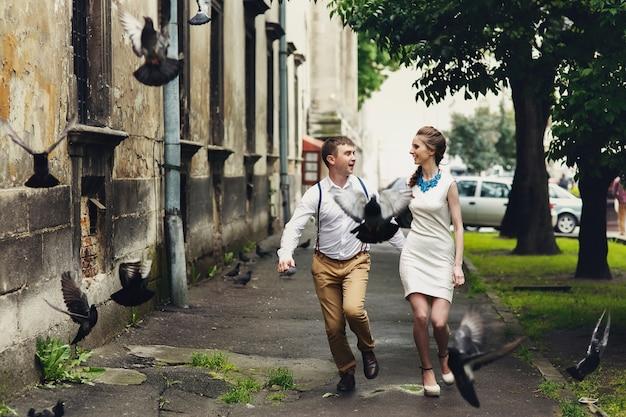 Голуби летают, прежде чем счастливая пара работает снаружи Бесплатные Фотографии