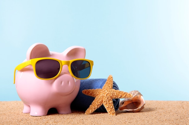 Piggy bank on a beach with sunglasses Free Photo