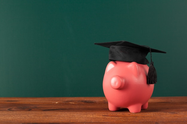 Piggy bank on blackboard . Premium Photo