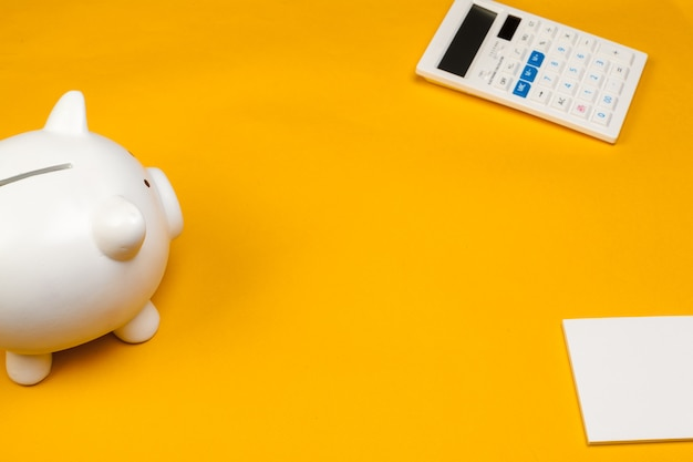 Piggy bank and calculator on yellow background Premium Photo