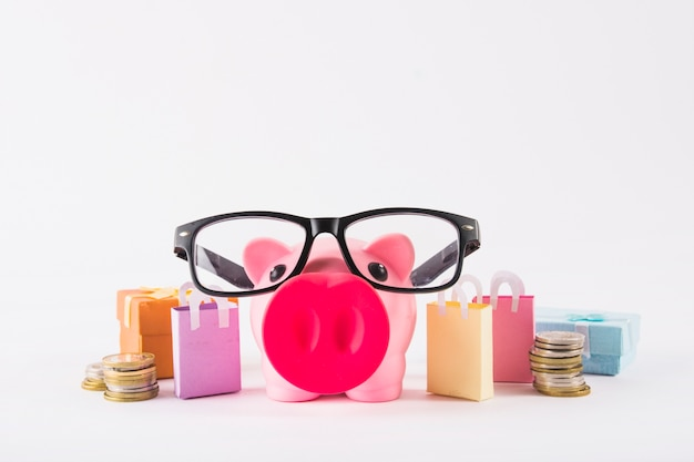 Piggy bank in glasses with paper bags Free Photo