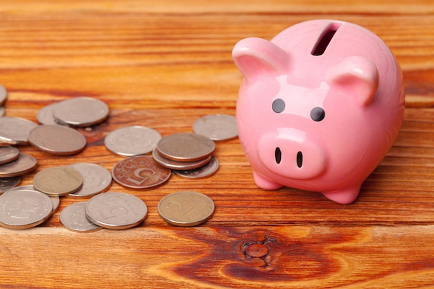Piggy bank with coin on wooden table Premium Photo