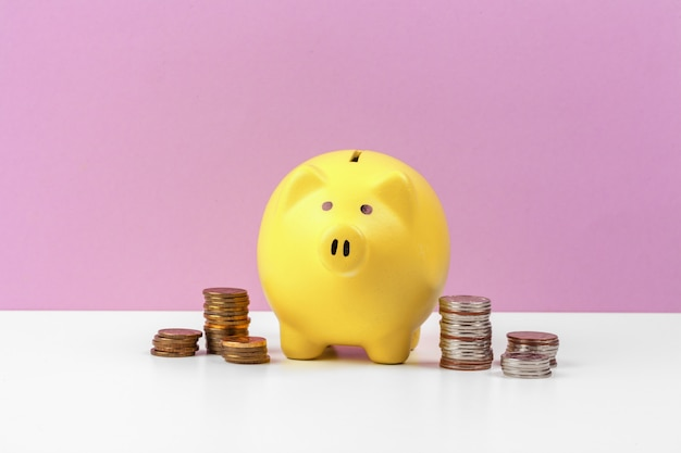 Piggy bank with coins on the table Premium Photo