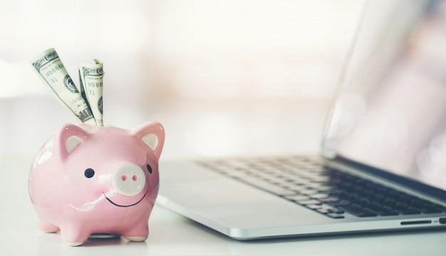 Piggy bank with laptop on the desk Premium Photo