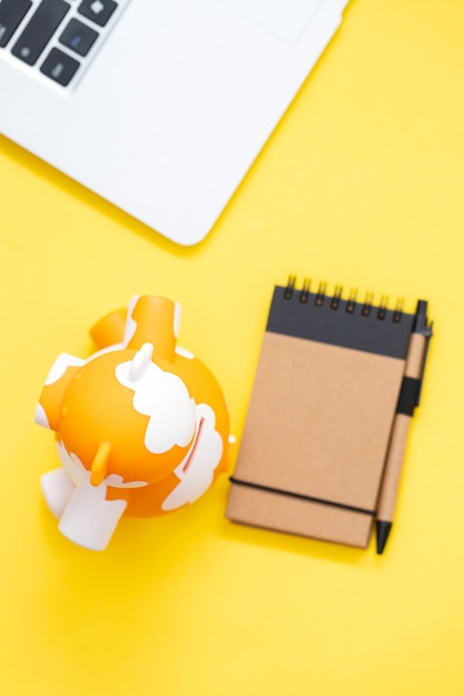Копилка с блокнотом и компьютером на желтом фоне Premium Фотографии