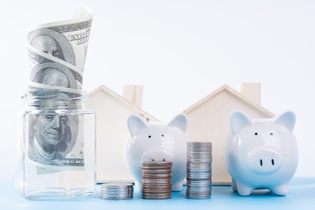 Piggy bank with stack coins and money paper inside jar and wooden house isolated grey background. property investment and house mortgage financial concept. Premium Photo