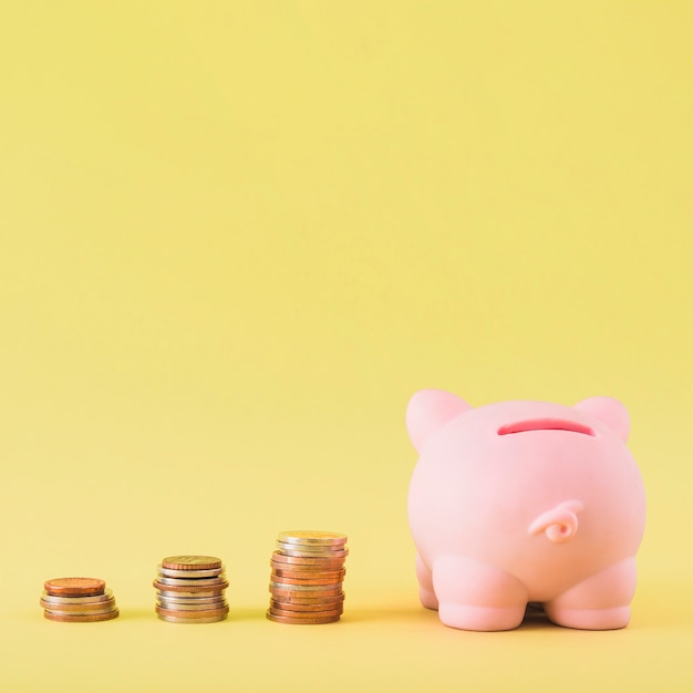 Piggy bank with stacks of coins Free Photo