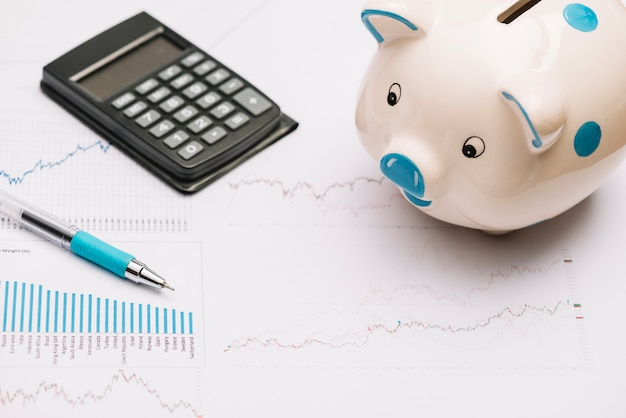 Piggybank; calculator and pen on stock market graph Free Photo