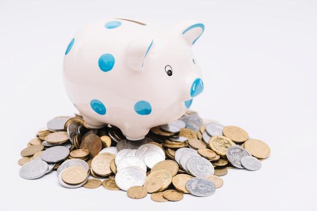 白い背景に多くの硬貨の上にpiggybank 無料写真