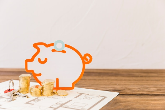 Piggybank with stacked coins and key on blueprint Free Photo