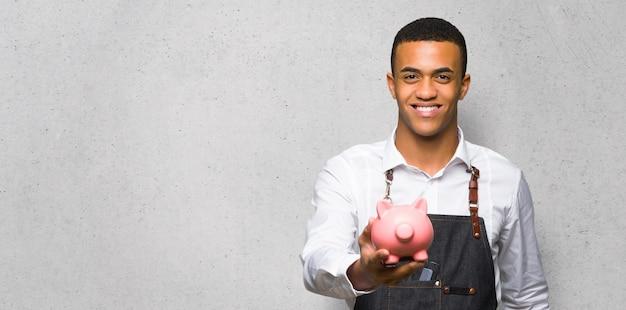 織り目加工の壁にpiggybankを保持している若いアフロアメリカン床屋男 Premium写真