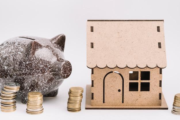 白い背景の段ボールの家の近くにコインのスタックとセラミックpiggybank 無料写真
