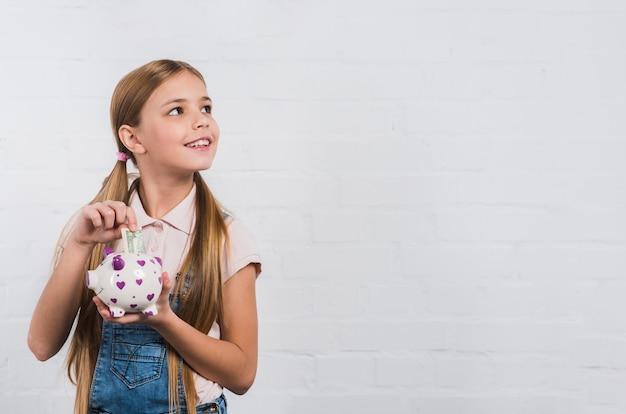 よそ見白いpiggybankで紙幣を挿入する微笑んでいる女の子の肖像画 無料写真