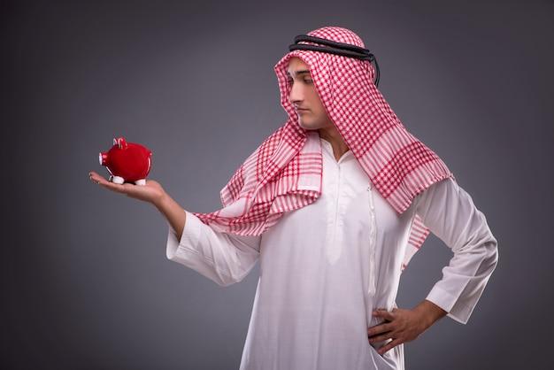 灰色のpiggybankとアラブのビジネスマン Premium写真