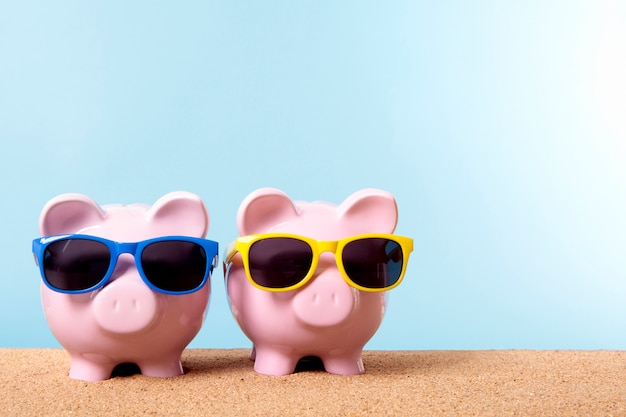 Piggybanks on a beach with sunglasses Free Photo