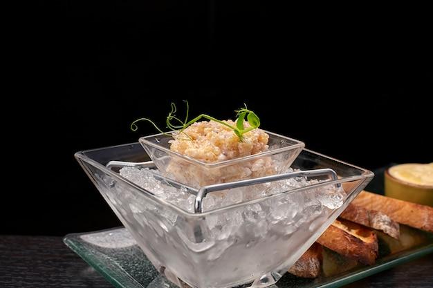パイクフィッシュキャビア、氷の上、クルトンとバター、透明な皿の上、暗い背景 Premium写真