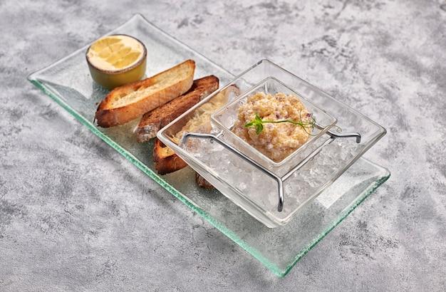 パイクの魚のキャビア、氷の上、クルトンとバター、透明な皿の上、白い背景 Premium写真
