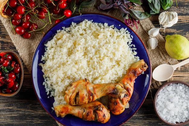 Плов с куриным мясом, вишней, солью, лимоном, базиликом, чесноком в тарелке на деревянном и кусочке мешка. Бесплатные Фотографии