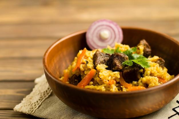 나무 테이블에 접시에 고기, 야채, 양파, 향신료와 필라프. 프리미엄 사진