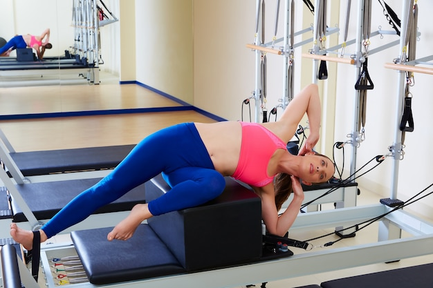 Pilates reformer woman short box side stretch Premium Photo
