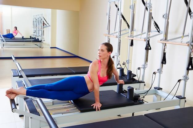 Pilates reformer woman snake twist exercise Premium Photo
