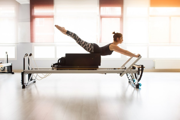 Pilates reformer workout exercises woman at gym indoor Premium Photo