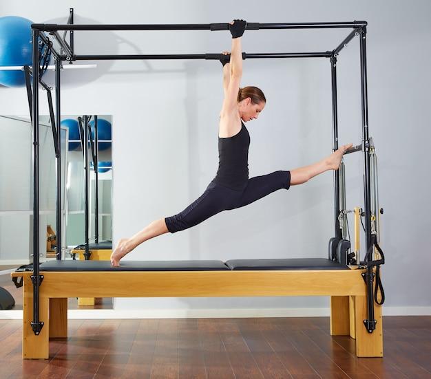Pilates woman in cadillac legs split reformer Premium Photo