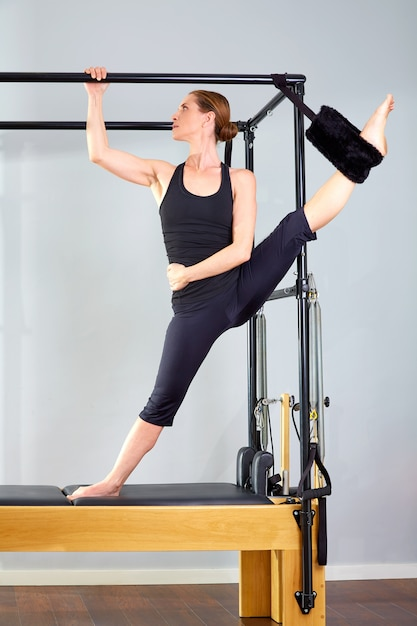 Pilates woman in cadillac split legs stretch exercise Premium Photo