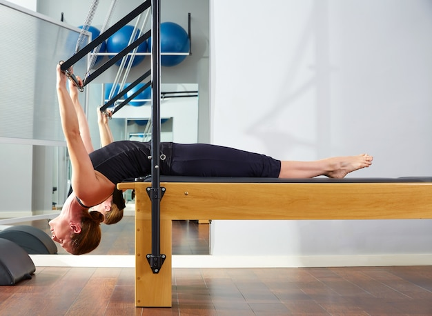 Pilates woman in reformer exercise at gym Premium Photo