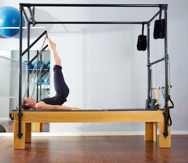 Pilates woman in reformer tower exercise at gym Premium Photo
