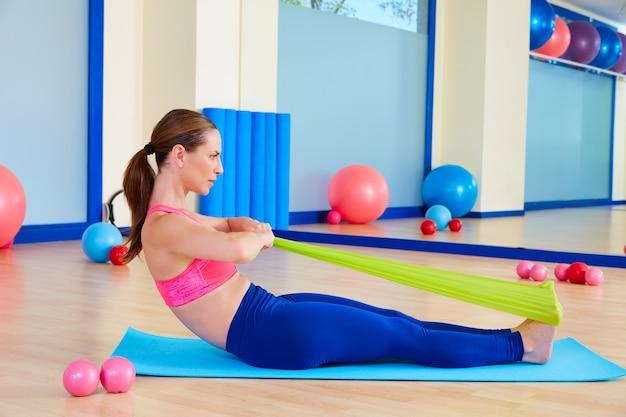Pilates woman rowing rubber band exercise Premium Photo