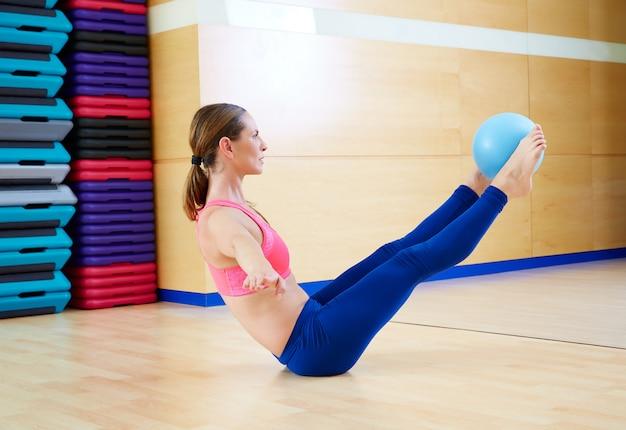 Pilates woman stability ball teaser exercise Premium Photo