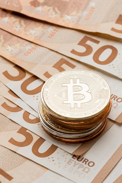 Pile of bitcoins on banknotes arrangement Free Photo