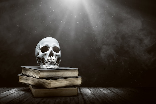 Pile of the book with a human skull on a wooden table Premium Photo
