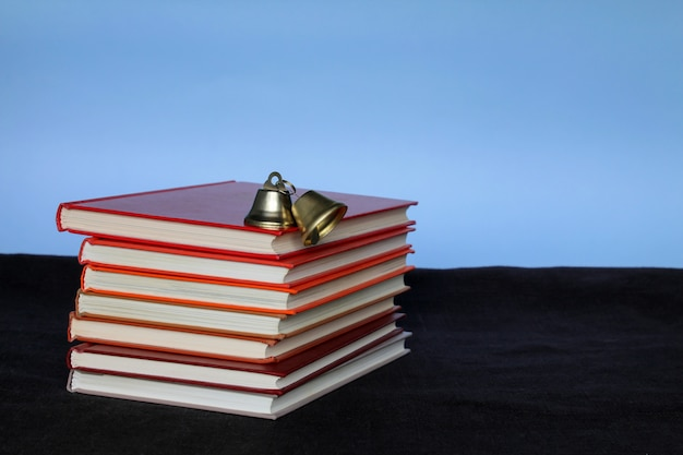 Pile of books and apple at the top on blue background Premium Photo