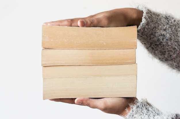 Pile of books between hands Free Photo