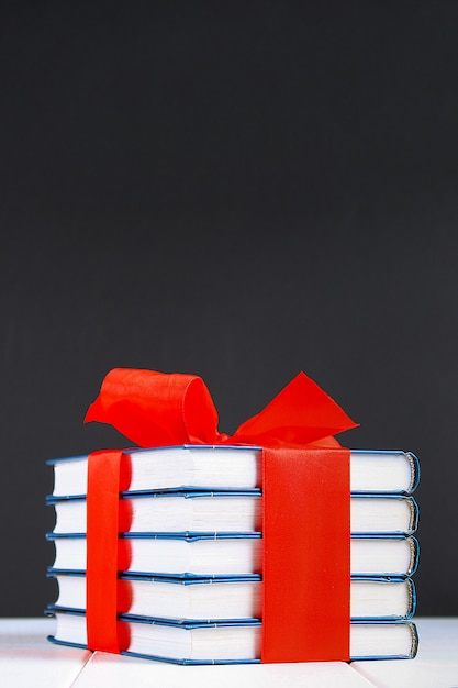 A pile of books tied with a red ribbon on a white wooden table. Premium Photo