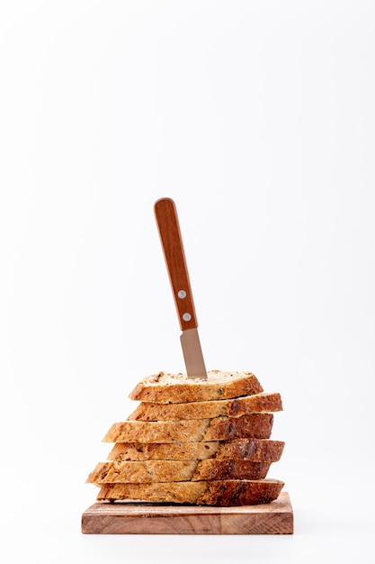 Pile of bread slices with knife on top Free Photo