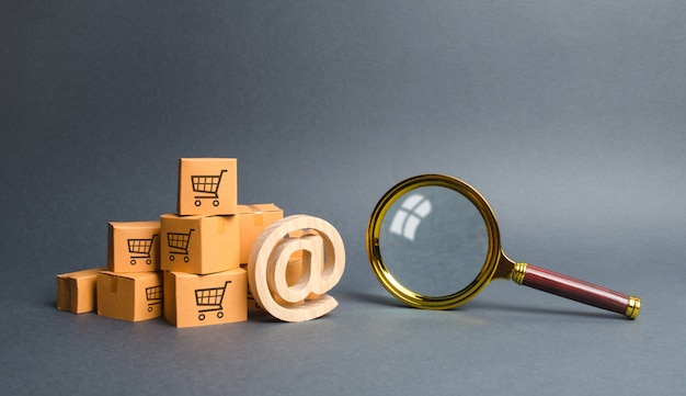 Pile of cardboard boxes with email symbol commercial at and magnifying glass Premium Photo