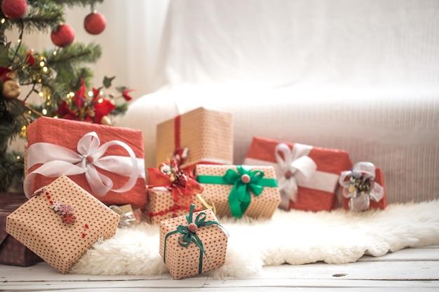 Pila di regali di natale sulla parete leggera sul tavolo di legno con tappeto accogliente. decorazioni natalizie Foto Gratuite