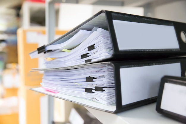 Pile of documents with black clips in folders stack up. Premium Photo