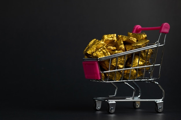 Pile of gold nuggets or gold ore in shopping cart or supermarket trolley on black background Premium Photo