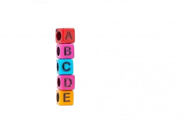 Pile of letter bead or beads with alphabet abcde on white background. Premium Photo